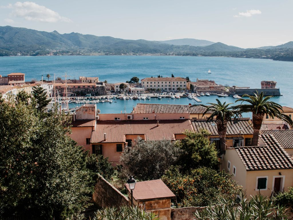 Von der Festung in Portoferraio aus haben Besucher der Insel Elba einen traumhaften Blick über Hausdächer und Palmen hinweg auf den sehenswerten Yachthafen. Im Hintergrund erheben sich die Berge der kleinen toskanischen Insel.