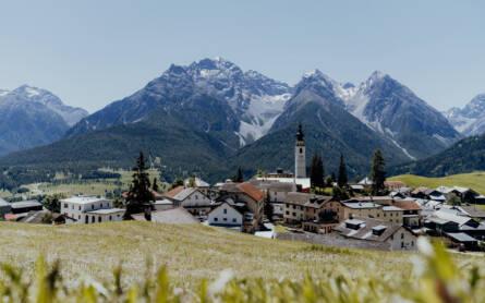 Blick über eine Wiese hinein in ein Dorf mit Kirchturmspitze, dahinter Bergpanorama, in Ftan in der Schweiz.