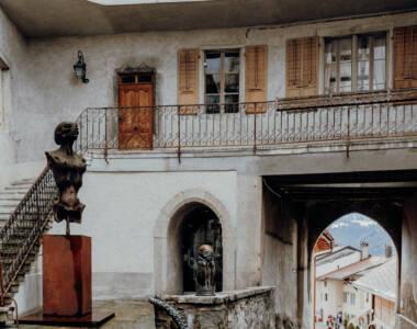 Häuserfassade und eine Statue in La Gruyère, Schweiz