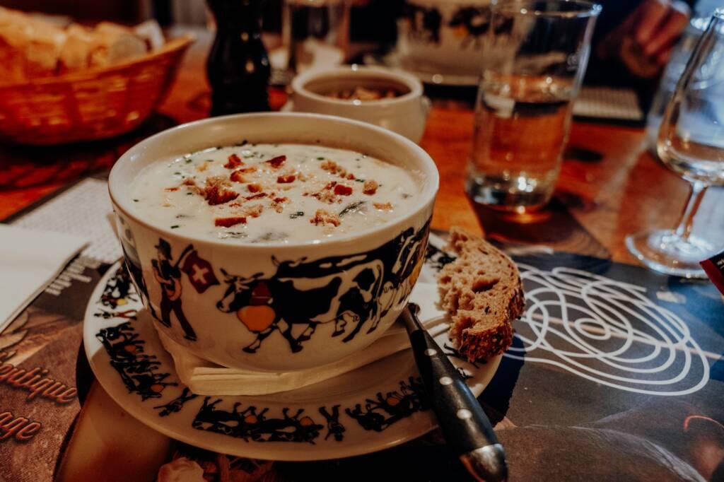 Eine Porzellanschüssel mit Kuhmotiv und geschmolzenem Käse und Croutons darin steht auf einem Teller angerichtet, auf dem ein Stück einer Scheibe Brot liegt.