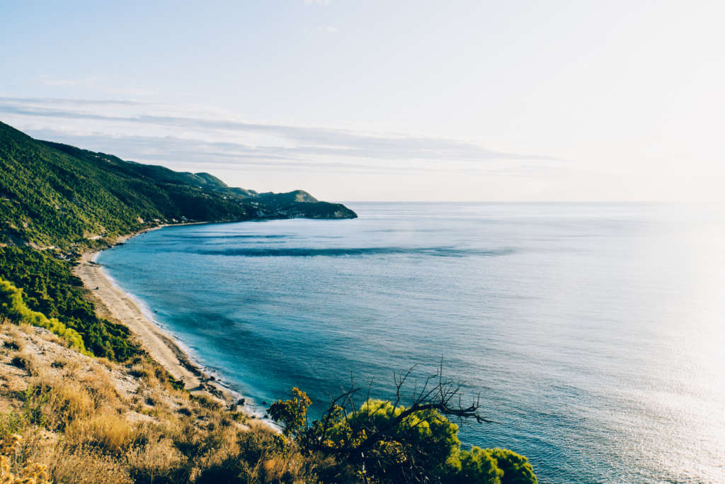 Eine Bucht auf Lefkada mit Sandstrand und türkisblauem Meer umgeben von begrünten Hügeln - ein Traum für jeden Urlauber.