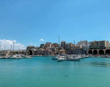 Zahlreiche Boote liegen im Hafen von Heraklion, der Hauptstadt von Kreta. Hinter dem Hafen stehen einige Hochhäuser.