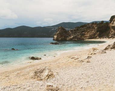 Sandstrand von Agiofili, blaues Meer und Felsen