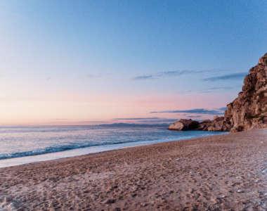 Der Sandstrand am Strand Kathisma leuchtet rot vom Sonnenuntergang am Himmel, das Meer leuchtet blau ohne Wellengang, der Himmel färbt sich vom Sonnenuntergang rot.