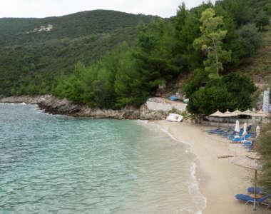 Blaue Liegen und Sonnenschirme aus Stroh liegen am Sandstrand von Afteli, das Meer ist türkisblau ohne Wellengang, über der Bucht erhebt sich eine grüne, bewaldete Hügellandschaft.