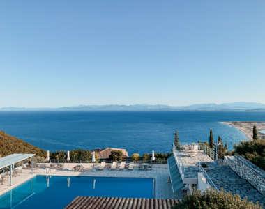 Der Pool im Mira Resort mit Liegen und Sonnenschirmen sowie überdachten Terrassen hat freie Sicht auf die Bucht und das Meer auf Lefkada, in der Ferne liegen die Berge.
