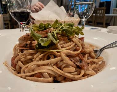 Auf einem Teller sind Nudeln mit Shrimps und Rucola oben drauf angerichtet, dahinter stehen ein Wasser- und ein Weinglas sowie ein Brotkorb.