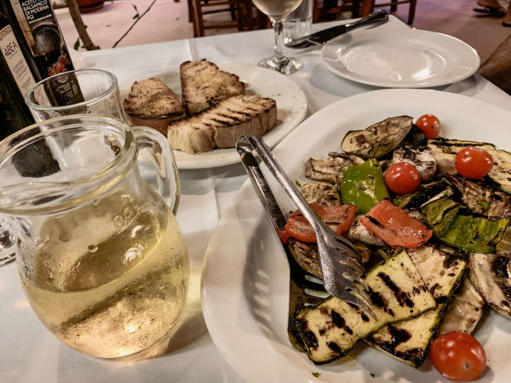 Auf einem Tisch angerichtetes Essen, geröstetes Gemüse, eine Karaffe mit Weißwein und Brot.