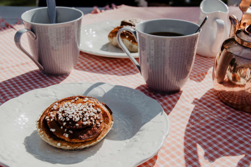 Auf einem Tisch mit rosa Tischdecke sind auf Tellern schwedische Gebäcke angerichtet, zwei Tassen Kaffee, eine Kaffeekanne und ein Kännchen stehen daneben.