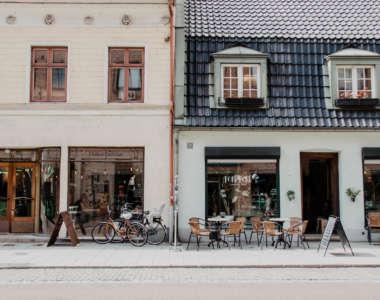Neben einer Straße stehen zwei Gebäude eng aneinander, vor beiden befinden sich draußen Stühle und Cafés im Inneren.