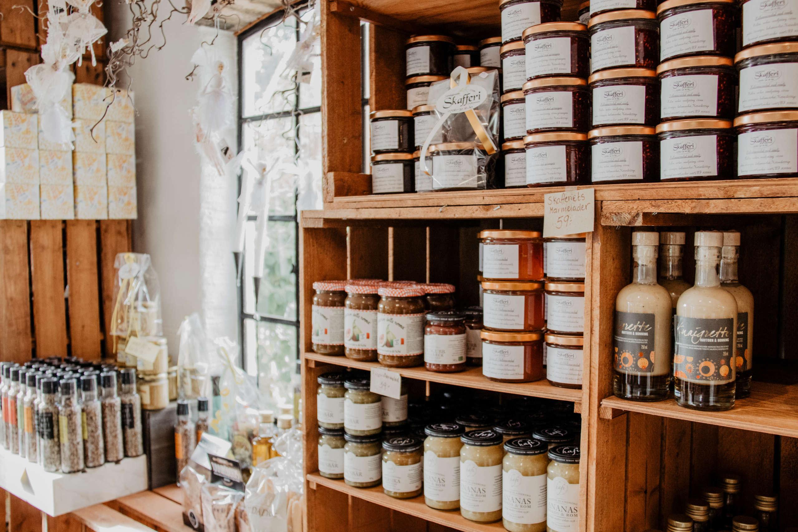 In einem aus vielen Weinkisten angerichteten Regal stehen allerlei Flaschen und Einmachgläser mit schwedischen Spezialitäten darin, auf der Anrichte daneben stehen Pfeffer- und Salzmühlen vor einem Fenster.