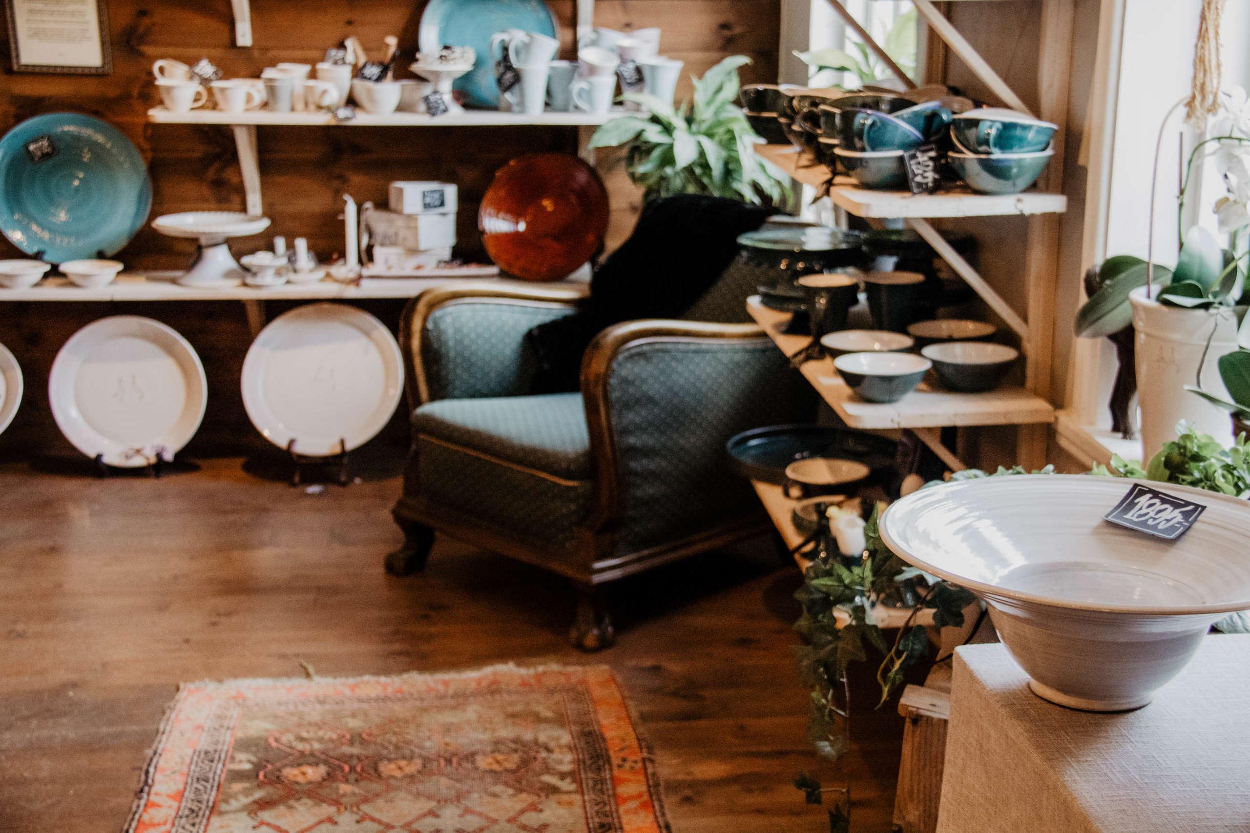 In einem kleinen Geschäft mit Holzboden steht ein großer dunkelbrauner Holzsessel mit grünem Polster, um ihn herum türmen sich allerlei Keramikwaren wie Teller, Tassen und Schüsseln auf.