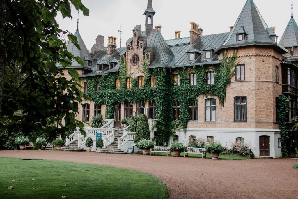 Das Schloss Sofiero liegt in einer grünen Parkanlage hinter einem roten Steinweg, das herrschaftliche Anwesen ist mit Efeu bewachsen und hat ein graues Dach, zwei Erker stehen hervor.