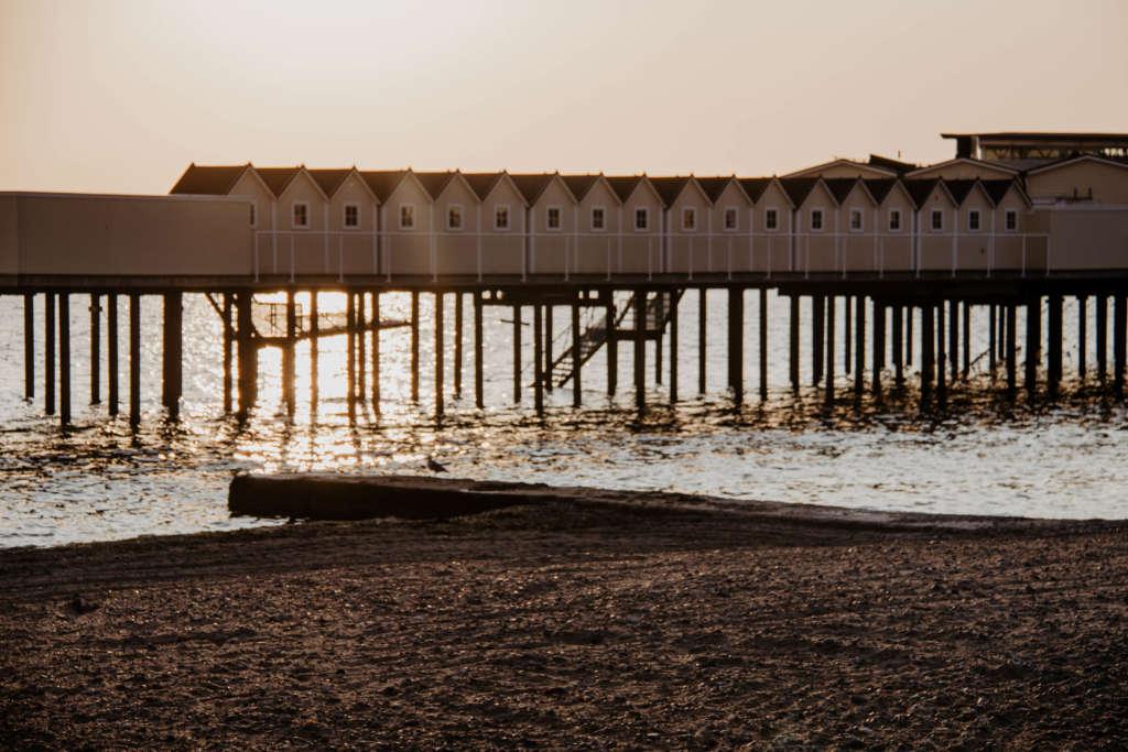 Eine lange Reihe von Häusern auf Stelzen, in denen sich Kaltbadehäuser befinden, liegen ein hohes Stück über dem seichten Wasser in der Abenddämmuerng, der Sand vom Strand vorne färbt sich dunkel im Licht, eine Treppe aus dem Wasser führt die weißen Häuser hinauf.