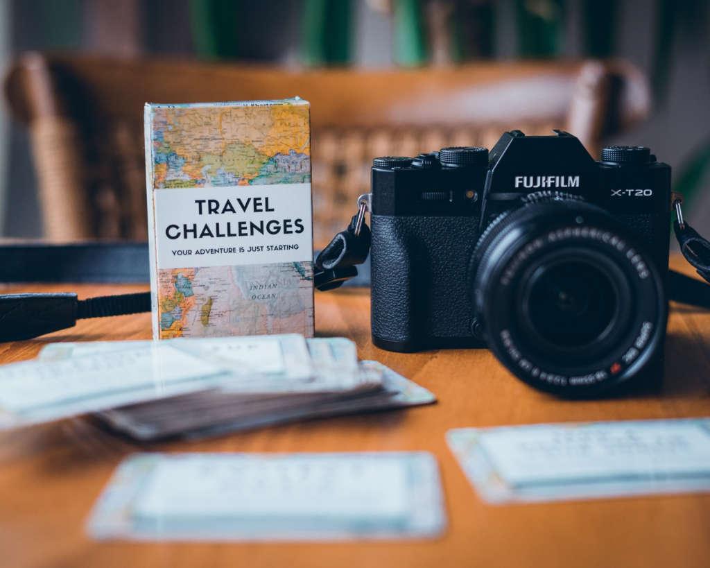 """Damit wird es auf Reisen nicht langweilig: Ein Buch voller kleiner Karten, auf denen """"Travel Challenges"""", also kleine zu bewältigende Aufgaben stehen, liegt einpackbereit neben der Kamera."""