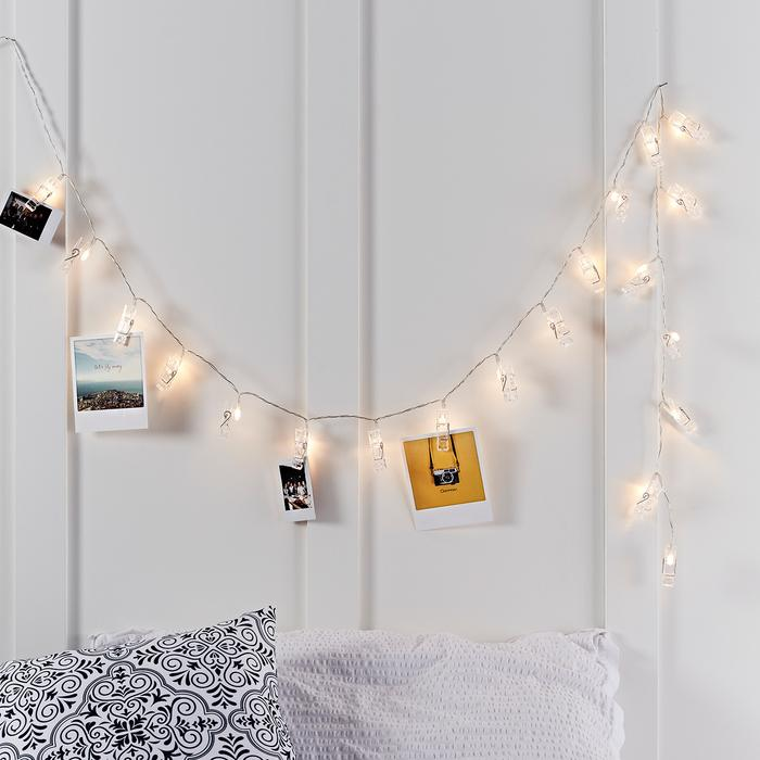 Ein dekoratives Geschenk für Reisefreunde: Bilder hängen an den Klammern einer mit LED-Leuchten ausgestatteten Lichterkette vor einer weißen Wand.