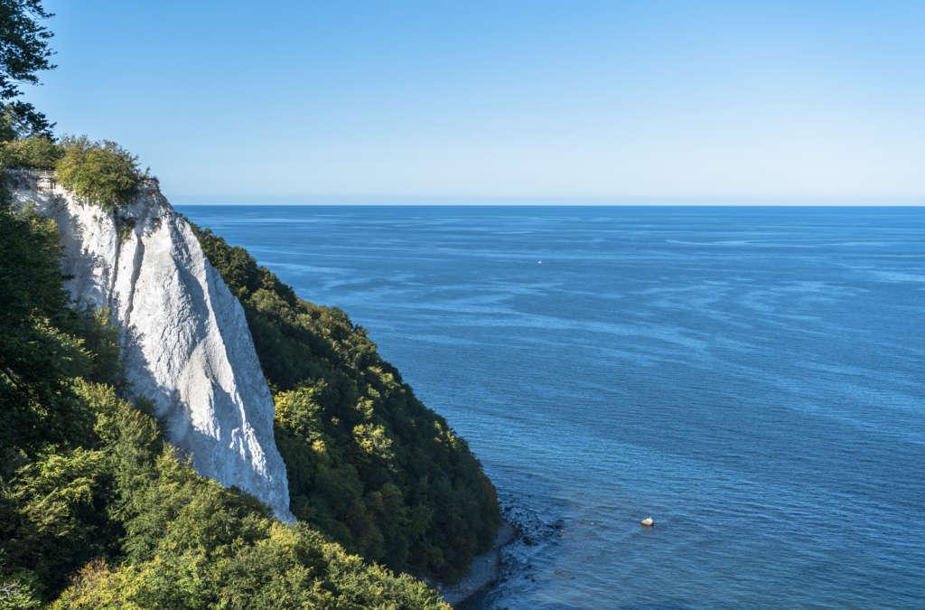Von einer hohen Plattform blickt man auf den weißen Kreidefelsen Königsstuhl auf Rügen, der grün bewachsen ist, rechts das blaue Meer und strahlender Himmel.