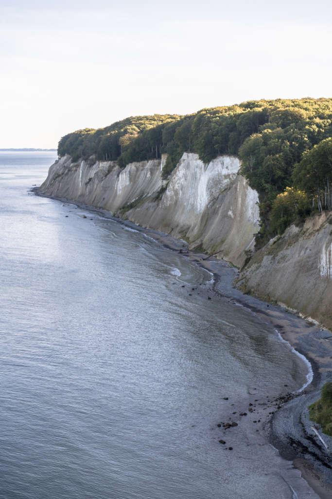 Vom Hochuferweg auf Rügen blickt man auf die kreideweiße Steilküste, die oben mit Gebüsch bewachsen ist, unten liegt das Meer.