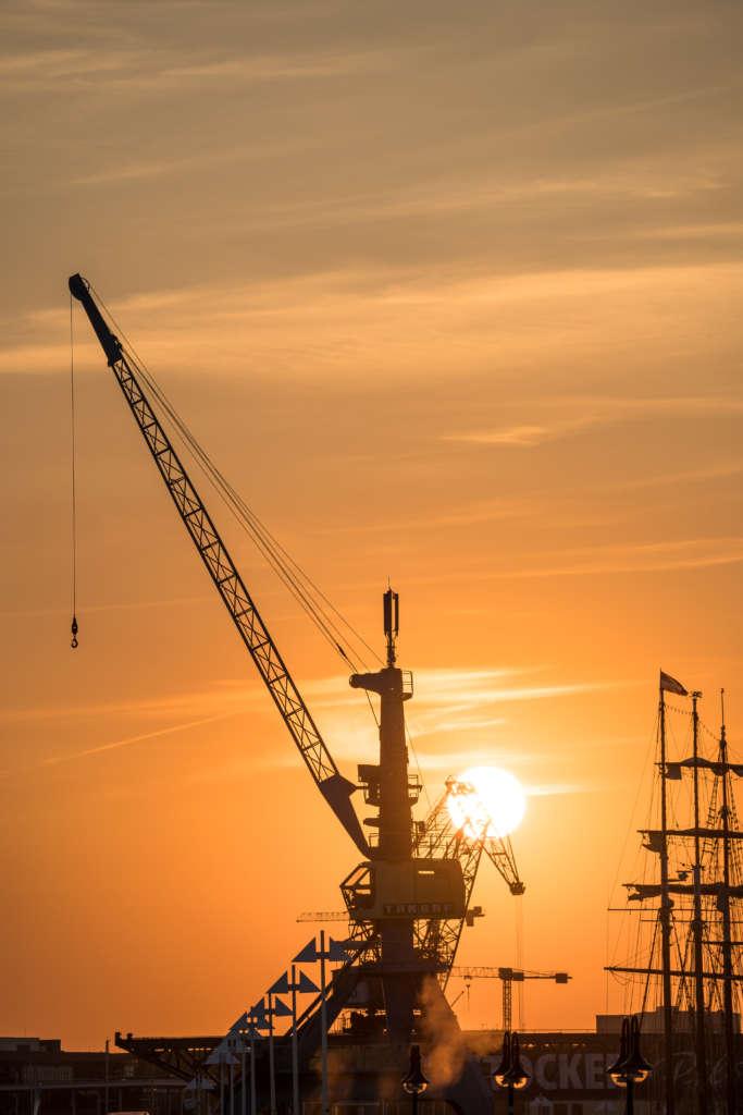 Ein alter Kran im Rostocker Hafen im Licht der untergehenden Sonne, der Himmel ist komplett orange gefärbt und wirft sein Licht auf den Kran.