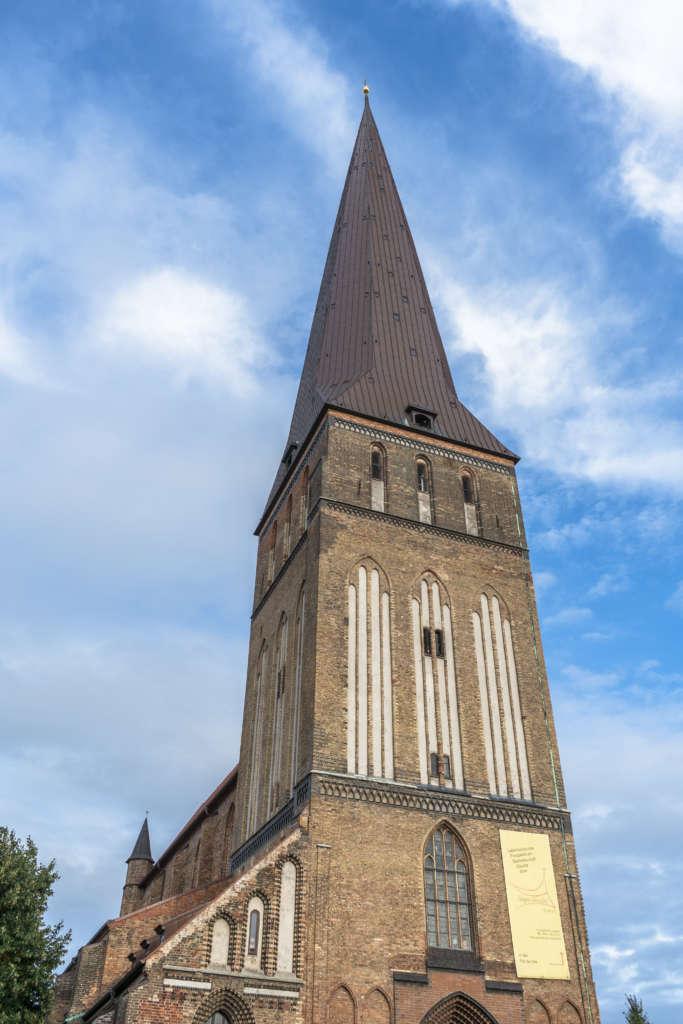 Die Rostocker Petrikirche erhebt sich in den strahlend blauen Himmel mit weißen Wolken, die braunen Backsteine sieht man aus der Froschperspektive.