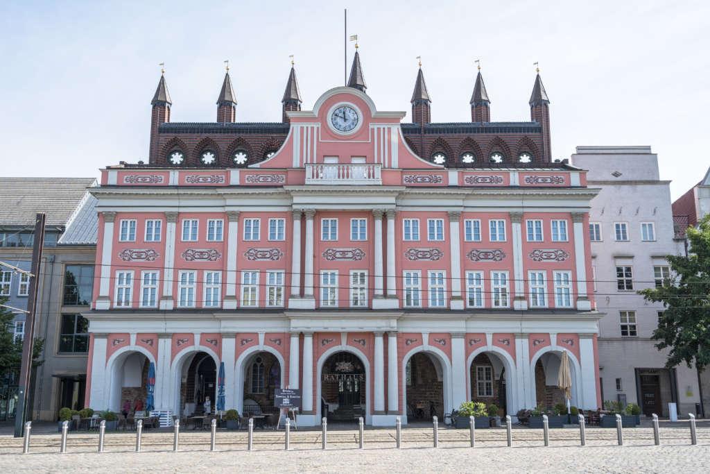 Das Rathaus von Rostock mit seiner rosafarbenen Fassade ist eine berühmte Sehenswürdigkeit der Stadt.