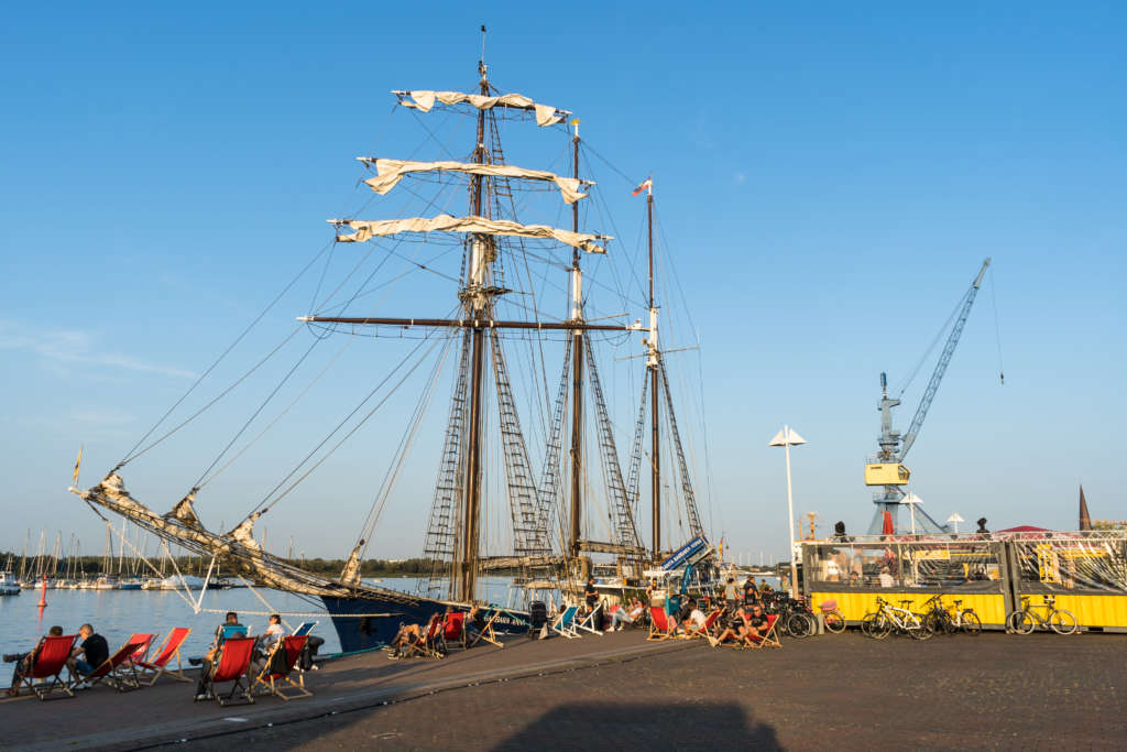 Ein umfunktioniertes Schiff liegt in Rostock an einem Dock an, davor sitzen Menschen in Strandstühlen, daneben befindet sich ein kleiner Unterstand mit anlehnenden Fahrrädern, der Himmel ist strahlend blau, man blickt auf einen Kran.