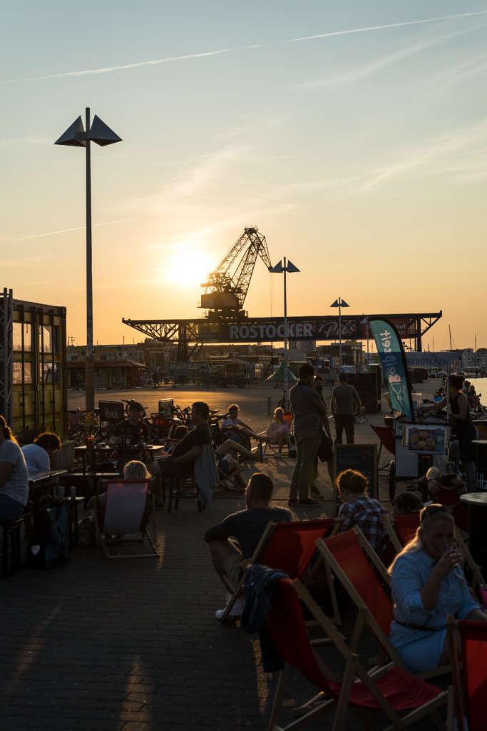 Im Sommer einen Besuch wert: Menschen sitzen in einer Bar am Hafen von Rostock bei Sonnenuntergang, im Hintergrund befindet sich ein Schiffskran.