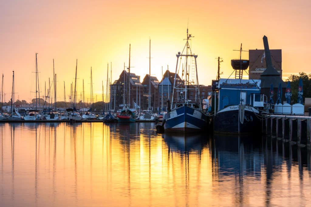 Diverse Schiffe, Yachten und Dampfer liegen bei Sonnenaufgang im Rostocker Stadthafen. die untergehende Sonne spiegelt sich im Wasser.