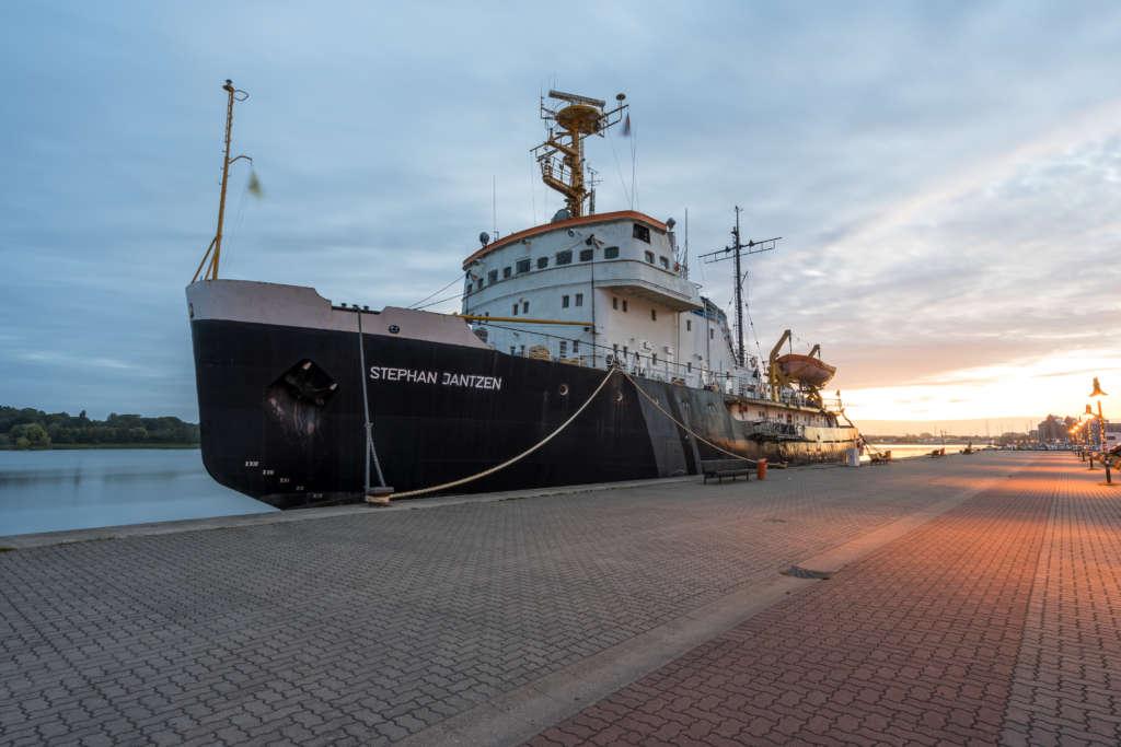 Die Stephan Jantzen, ein riesiger Eisbrecher, liegt im Hafen von Rostock, im Hintergrund geht die Sonne auf, das Schiff dockt an eine gepflasterte Plattform, die mit Straßenlaternen gesäumt ist, an.