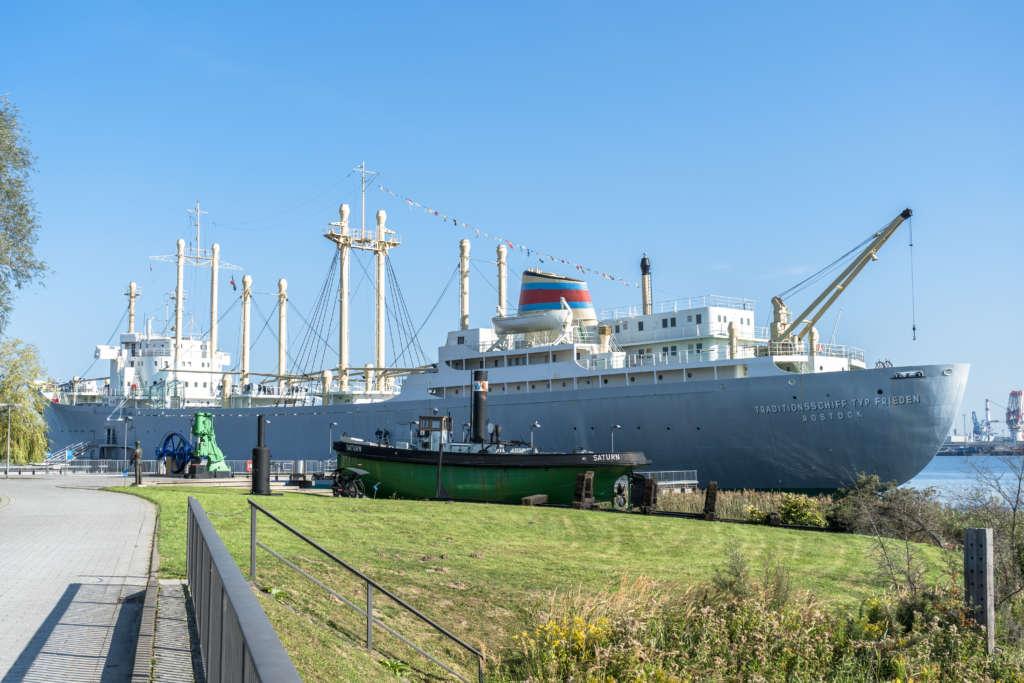 Das Traditionsschiff Typ Frieden liegt am Ufer von Rostock an, vor ihr liegt ein kleines grünes Boot, davor Gras und gepflasterter Weg, strahlend blauer Himmel.