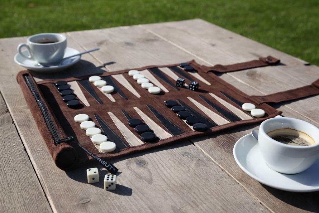 Für gemeinsame Spiele auf Reisen: Das Backgammon in einer leichten Ledertasche zum Aufrollen liegt auf dem Tisch ausgebreitet, die Spielsteine sind platziert.