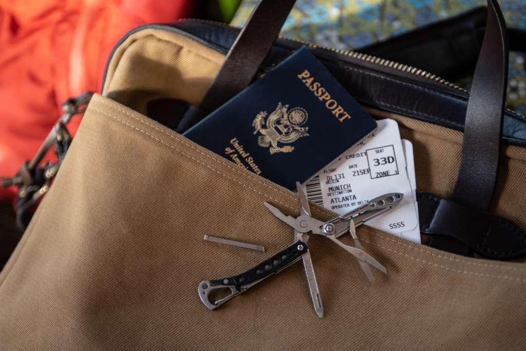 Ein nützlicher Begleiter auf Reisen: Das Multitool, das hier auf einer braunen Umhängetasche neben dem Reisepass und den Flugtickets liegt.