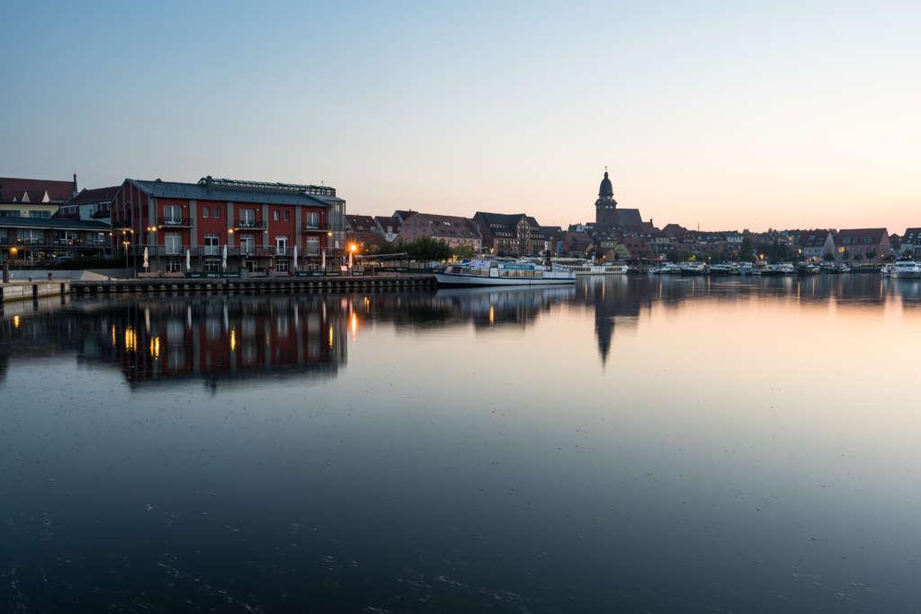 Die Stadt Waren an der Müritz liegt im Sonnenaufgang am Wasser, rote Häuser, eine Kirche und anlegende Schiffe sind in der Dämmerung zu erkennen.