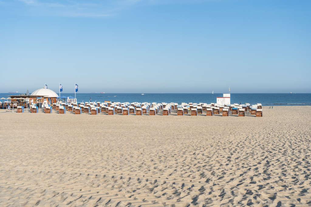 Sandstrand in Warnemünde mit Blick aufs Meer und Strandkörbe.