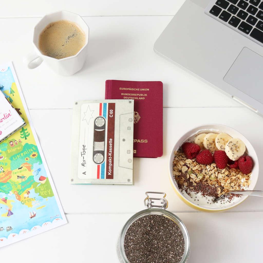 Auf einem Tisch liegen angerichtet eine Schüssel mit Müsli, ein Weckglas mit Chia-Samen, eine Kaffeetasse, ein Laptop, ein Reisepass, sowie die passende Reisepasshülle in Form einer Musikkassette.