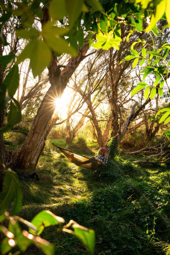 In der Hängematte aus ultraleichtem Gewebe liegt ein Mann zwischen zwei Bäumen und genießt die Sonnenstrahlen, die durch die Zweige hindurchscheinen - ein Traum für jeden Backpacker.