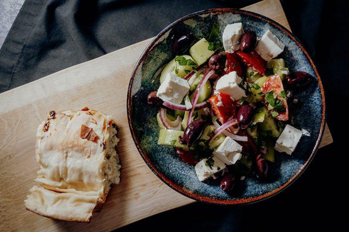 Die griechische Spezialität Tyropita, ein gefülltes Fladenbrot, mit Salat bestehend aus Feta, Oliven, Zwiebeln und Tomaten wird in Griechenland und weltweit gern zubereitet.