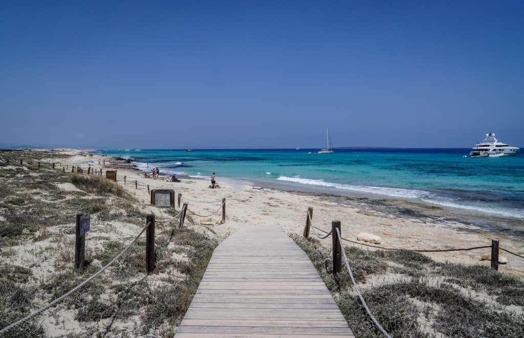Ein Holzweg führt an einen unberührten Strand von Formentera.