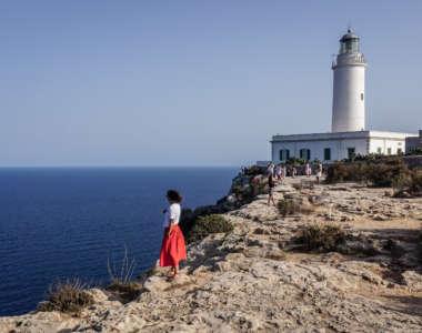 Reisebloggerin Eva von HiddenGem blickt an einer Klippe auf das endlose Meer vor Formentera, hinter ihr liegt eine wichtige Sehenswürdigkeit der Insel, der Leuchtturm Far de la Mola.