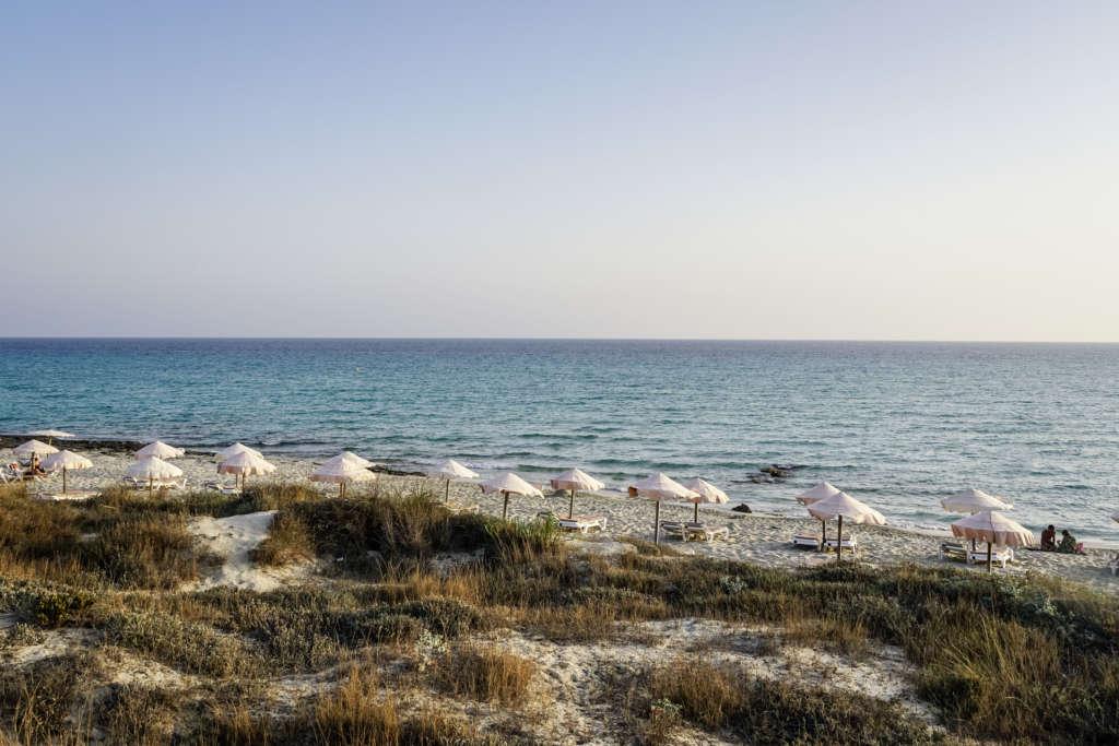 Die Strände von Formentera liegen malerisch in wunderschönen Buchten mit weißen Schirmen - die Insel ist noch ein echter Geheimtipp.