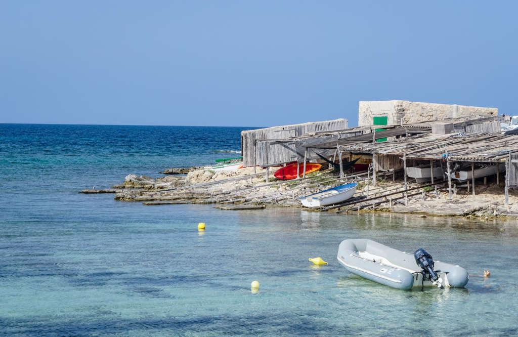 Hübsche Fischerhütten und Trockendocks aus Holz liegen malerisch in der Bucht von Es Pujol auf Formentera.