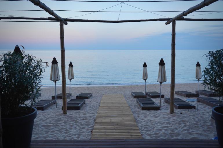 Der Sandstrand von Radjana Beach zum Sonnenaufgang mit Strandliegen und Sonnenschirmen - ein unbekannter Strand in Bulgarien.