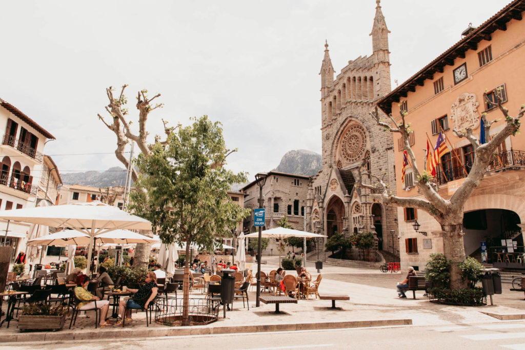 Der belebte Plaça Constitució in Sóller mit Menschen unter Sonnenschirmen und Blick auf die Kirche Sant Bartomeu auf Mallorca.