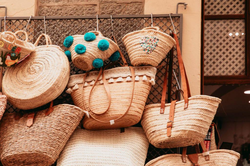 Mehrere Strohtaschen verschiedener Größen und Designs, die an einem Gitter zum Verkauf im Alameda Shop hängen, laden zum Shoppen in Sóller auf Mallorca ein.