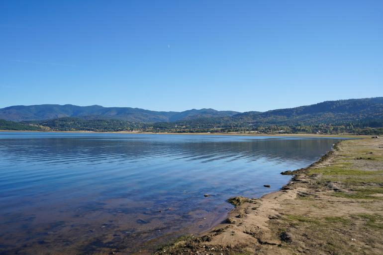 Ein ruhiger See in der Stadt Welingrad in Bulgarien umgeben von Wäldern mit kleinem felsigen Ufer.