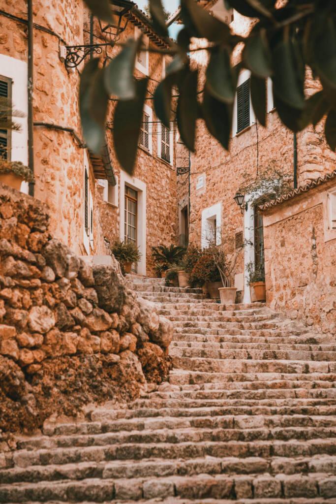Eine Steintreppe in Fornalutx, die zu einem idyllischen Gebäude hinaufführt, umrahmt von Blättern, zieht sich romantisch durch eines der schönsten Dörfer Mallorcas.