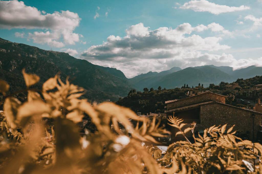 Durch Blätter blickt man von Fornalutx aus auf Berge und die Serra Tramuntana auf Mallorca.