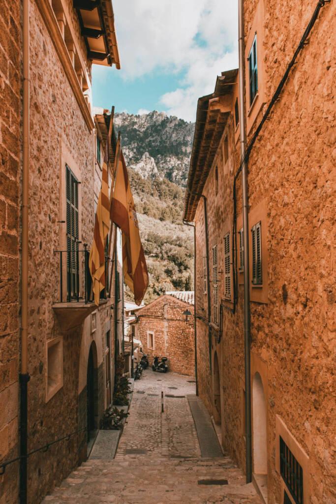 Blick durch eine kleine Gasse in Mallorcas ruhigem Ort Fornalutx auf die Berge der Tramuntana.