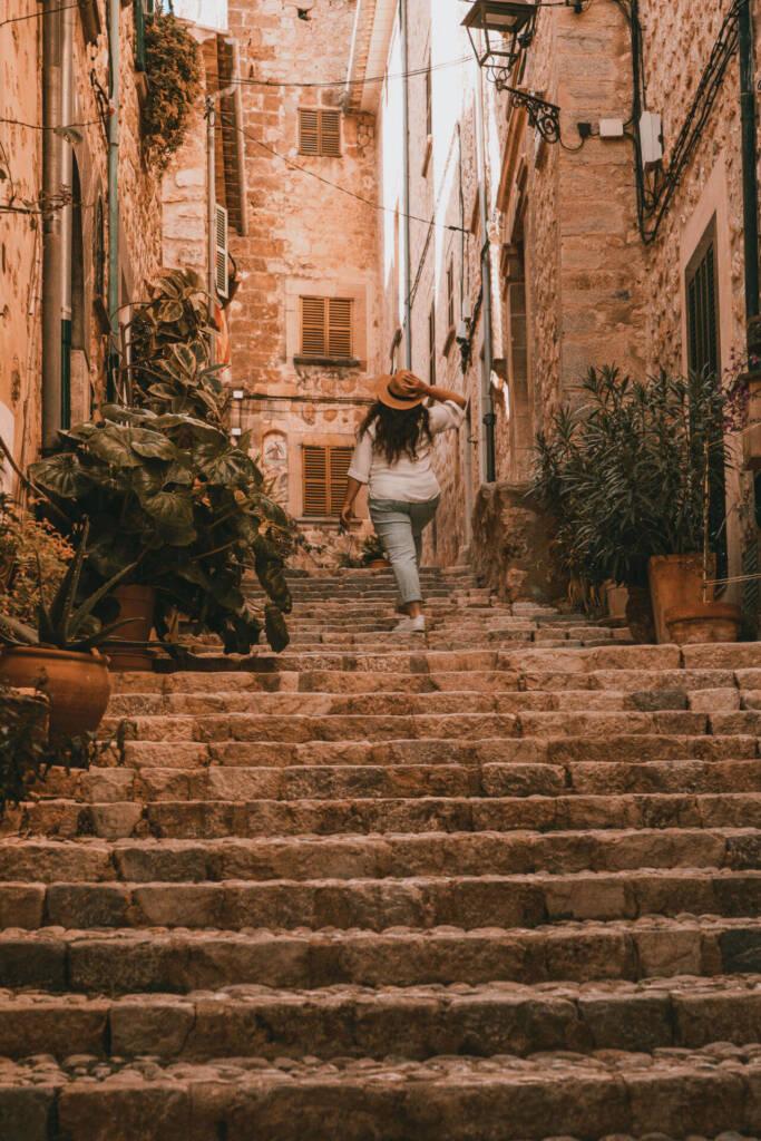 Reisebloggerin Tatiana von Thehappyjetlagger steigt die Stufen einer kleinen bewachsenen Gasse in Mallorcas schönem Dorf Fornalutx hinauf.