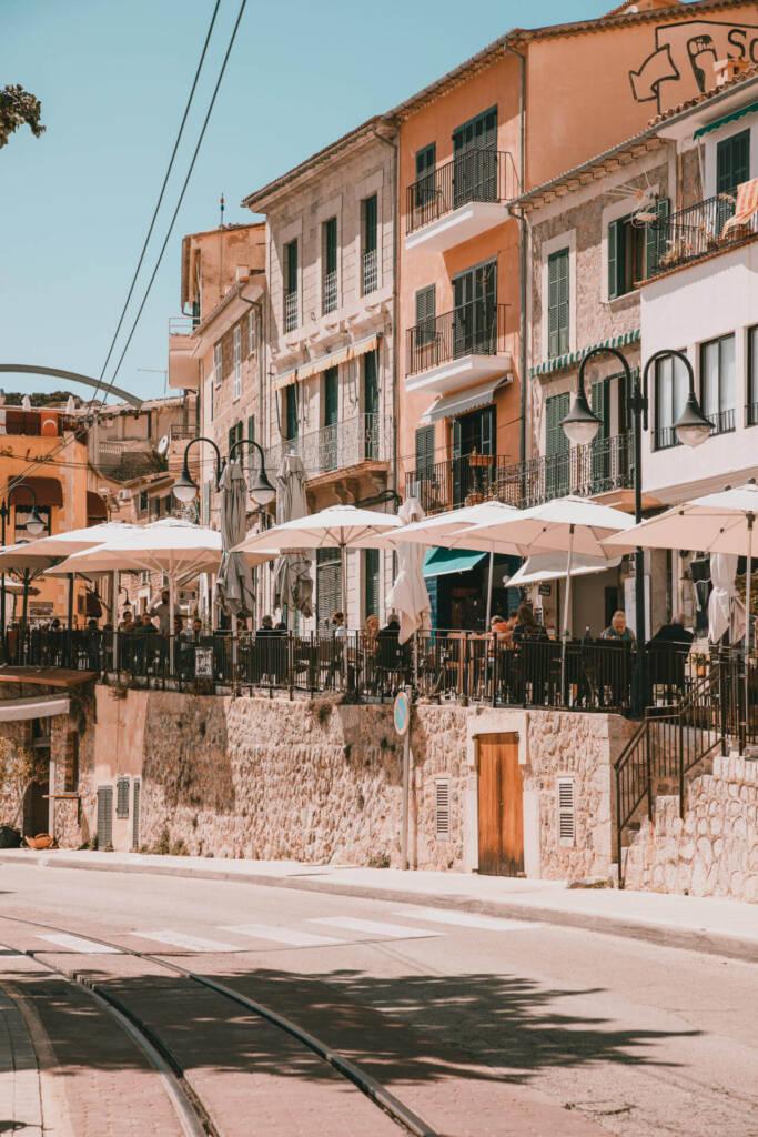 Eine belebte Straße mit Terrassen, die den Berg hinaufführt, bietet den perfekten Blick über den Hafen des Dorfs Sóller auf Mallorca.